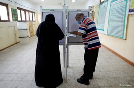 People cast their ballots at a school used as a polling station during the second round of Egypt's parliamentary elections.