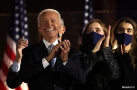 Democratic 2020 U.S. presidential nominee Joe Biden applauds next to his granddaughters after speakig during his election rally.