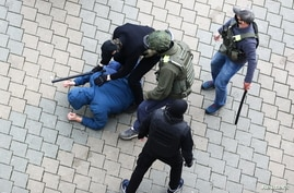 Unidentified people, who are presumably Belarusian law enforcement officers, restrain a man during a rally to reject the…
