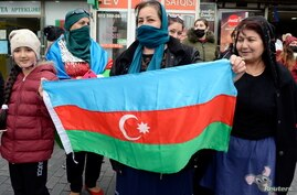 People hold the national flag as they celebrate on the streets after Azerbaijan's President Ilham Aliyev said the country's…