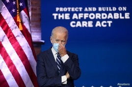 U.S. President-elect Joe Biden adjusts his face mask after delivering remarks about health care and the Affordable Care Act.