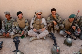 FILE PHOTO: A U.S. Marine(C) talks with Afghan National Army (ANA) soldiers during a training in Helmand province, Afghanistan,…