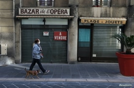 A woman walks his dog past a closed shop on sale during the second national lockdown as part of the measures to fight a second…