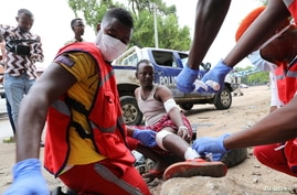 Paramedics attend to a man injured at the scene of a suicide explosion at a restaurant near a police academy, in Mogadishu,…