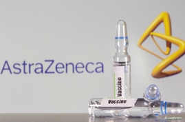 FILE PHOTO: A test tube labeled with the vaccine is seen in front of AstraZeneca logo in this illustration taken, September 9,…