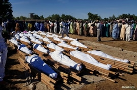 Men gather near dead bodies of people who were killed by militant attack, during a mass burial at Zabarmari, in the Jere local…
