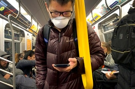 In this March 12, 2020 photo, a commuter wears a mask while riding the subway in New York.