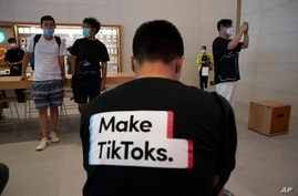 FILE - In this July 17, 2020, file photo, a man wearing a shirt promoting TikTok is seen at an Apple store in Beijing, China…