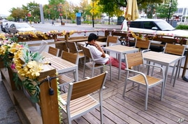 A person sits at an outdoor table in Montreal, Monday, Sept. 28, 2020. (Paul Chiasson / The Canadian Press via AP)