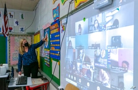 Jennifer Lepore wears a face mask teaches a Kindergarten class to students participating remotely and in person at School 16,…