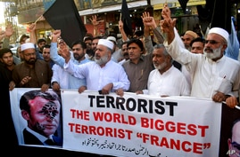 Pakistan traders hold a banner with a defaced picture of French President Emmanuel Macron during a protest against the…