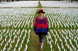 FILE - Artist Suzanne Brennan Firstenberg walks among thousands of white flags planted in remembrance of COVID deaths.