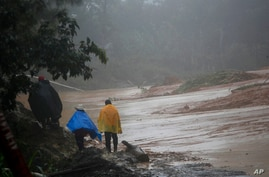 People walk around a road blocked by a landslide in San Cristobal Verapaz, Saturday, Nov. 7, 2020, in the aftermath of…