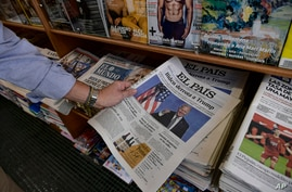 A man picks up a Spanish newspaper reporting on President-elect Joe Biden winning the US presidential election, in Pamplona,…