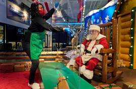 LaToya Booker cleans a transparent barrier between visitors for Santa at a Bass Pro Shop in Bridgeport, Conn., Tuesday, Nov. 10…