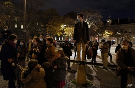 French believers stand and chant religious songs in front of Saint Sulpice Catholic church, in Paris, Nov. 13, 2020.