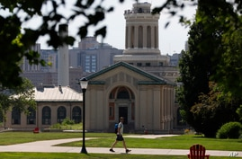 FILE - In this file photo from June 7, 2019, a man walks by Hamerschlag Hall on the Carnegie Mellon University campus in Pittsburgh.