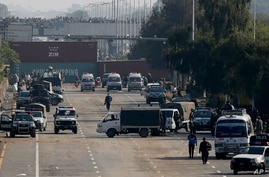 Security vehicles park near shipping containers placed by authorities on a highway to stop supporters of the 'Tehreek-e-Labaik…