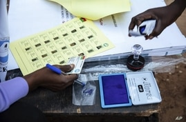 Election officials check identification papers of people who lined up to vote in Burkina Faso's presidential and legislative elections, as polling stations open in Ouagadougou, Nov. 22, 2020.