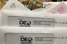 Envelopes from the Florida Department of Economic Opportunity Reemployment Assistance Program are shown, Nov. 5, 2020, in Surfside, Florida.