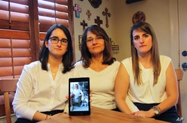 FILE - In this Feb. 15, 2019 file photo, Dennysse Vadell sits between her daughters Veronica, right, and Cristina holding a…