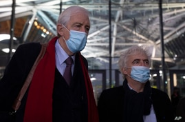 Lawyers George Henri Beauthier, left, and William Bourdon, right, representing the National Council of Resistance of Iran, speak with the media as they arrive at the courthouse in Antwerp, Belgium, Nov. 27, 2020.