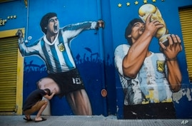 Augusto Canosa prays while touching a painting of Diego Maradona near the Boca Juniors stadium in Buenos Aires, Argentina,…