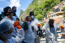 Volunteers hold hands in prayer before they begin a disinfection operation to help contain the spread of the new coronavirus at the Santa Marta slum, in Rio de Janeiro, Brazil, Nov. 28, 2020.