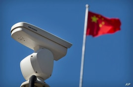 A Chinese flag flies near a Hikvision security camera monitoring a traffic intersection in Beijing, Tuesday, Oct. 8, 2019. The…