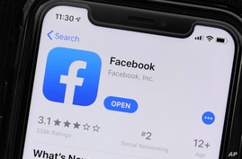 FILE - This July 30, 2019 file photo shows an update information of Facebook application on a mobile phone displayed at a store…