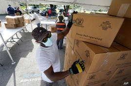 City worker Randy Greice, foreground, unloads a pallet of food at a food distribution event, Oct. 6, 2020, in Opa-locka, Florida.