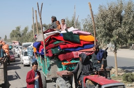 Afghan families leave their houses after fighting between the Afghan military and Taliban insurgents in Helmand province,…