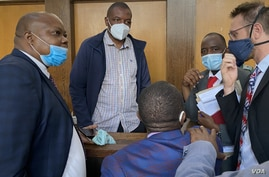Journalist Hopewell Chin'ono talks to his lawyers Nov. 12, 2020, after Magistrate Marehwanazvo Gofa denied him bail on grounds that he had high propensity to abuse social media again. (Columbus Mavhunga/VOA)