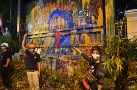 Pro-democracy protesters pose next to a paint-splattered sign for the police headquarters, during an anti-government rally in Bangkok, Thailand, Nov. 18, 2020.