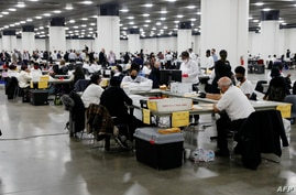 Election workers count absentee ballots sent in for the 2020 U.S. election at TCF Center in Detroit, Michigan, Nov. 4, 2020.