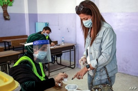 A voter, mask-clad due to the coronavirus pandemic, dips her finger in ink after voting at a polling station in Jordan's capital Amman, Nov. 10, 2020.