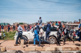 Musician-turned-politician Bobi Wine (on top of car) greets supporters as he makes his way to be officially nominated as a presidential candidate, in Kampala, Uganda, Nov. 03, 2020.
