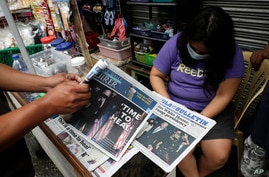 FILE - A man buys a newspaper at a makeshift stand after Joe Biden was projected the winner of the 2020 U.S. presidential election, in Manila, Philippines, Nov. 9, 2020.