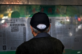 A man reads a newspaper reporting on the U.S. presidential election, at a stand in Beijing, China, Nov. 5, 2020.