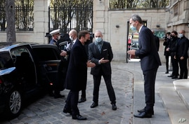 French President Emmanuel Macron, left, is welcomed by Deputy Head of Mission at the Austrian embassy Wolfgang Wagner in Paris before signing a condolence book for victims of the Vienna attack, Nov. 3 2020.