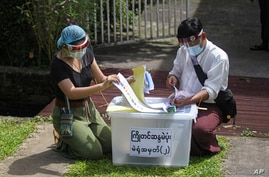 Officers from Union Election Commission arrange ballots for an early voting for upcoming Nov. 8 general election outside a residence on the outskirts of Yangon, Myanmar, Oct. 29, 2020.