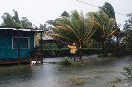 A man fixes the roof of a home surrounded by floodwaters brought on by Hurricane Eta in Wawa, Nicaragua, Nov. 3, 2020.