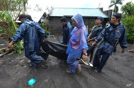 Rescuers carry the body of a man who drowned in floods as Typhoon Goni hit Guinobatan, Albay province, central Philippines, Nov. 1, 2020.