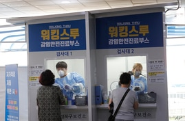 FILE - Medical workers in a booth take samples from people for COVID-19 tests at a makeshift clinic in Seoul, South Korea,  Aug. 20, 2020.