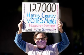 Demonstrator Gina Dusterhoft holds up a sign as she walks to join others standing across the street from the federal courthouse in Houston, Texas, Nov. 2, 2020, before a hearing involving drive-thru ballots cast in Harris County.