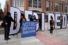 People hold signs outside the Wisconsin Center before a Milwaukee hand recount of presidential votes, in Milwaukee, Wisconsin, Nov. 20, 2020.