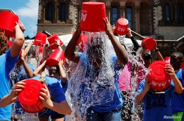 """FILE - People pour buckets of ice water over her heads as part of the """"ALS Ice Bucket Challenge,"""" a viral activity started by Pat Quinn and Pete Frates to raise money for research into the ALS disease, in Boston, Massachusetts, July 15, 2019."""