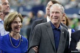 FILE - Former U.S. President George W. Bush smiles during a presentation with former first lady Laura Bush at a football game at AT&T Stadium, in Arlington, Texas, Oct 6, 2019. (Tim Heitman-USA TODAY Sports)