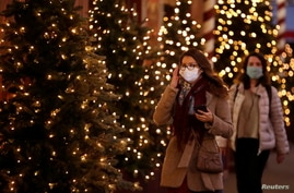 FILE - Women, wearing protective face masks, walk past illuminated Christmas trees in a street in Paris, France, Nov. 12, 2020.