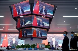 China's President Xi Jinping is seen on screens in the media center as he speaks at the opening ceremony of the third China International Import Expo (CIIE) in Shanghai, Nov. 4, 2020.